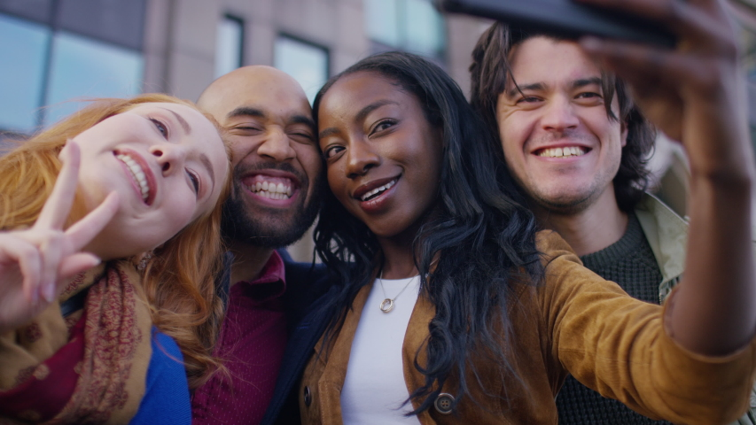 Diverse group of friends post together for a selfie on a cell phone #1029480425