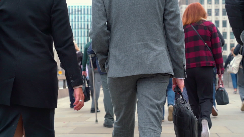 Crowd of pedestrian commuters crossing London Bridge on their way to work on cool morning in early May.  Slow motion version – real time version also available. Clip 17a of 66 joins to 17b | Shutterstock HD Video #1029484475