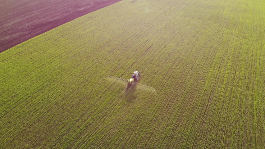 Aerial view of farming tractor spraying on field with sprayer, herbicides and pesticides at sunset. Farm machinery spraying insecticide to the green field, agricultural natural seasonal spring works. | Shutterstock HD Video #1029535685
