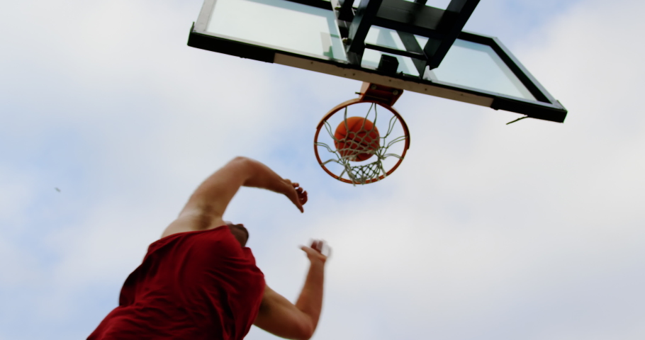 Low angle view of Caucasian basketball player playing basketball in basketball court 4k #1029607775