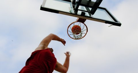 Low angle view of Caucasian basketball player playing basketball in basketball court 4k