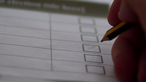 Close Up Detail Of Man Voting In Booth, Crossing With Pencil.