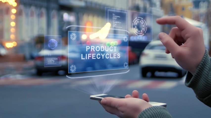 Female hands on the street interact with a HUD hologram with text Product lifecycles. Woman uses the holographic technology of the future in the smartphone screen on the background of city | Shutterstock HD Video #1029623165
