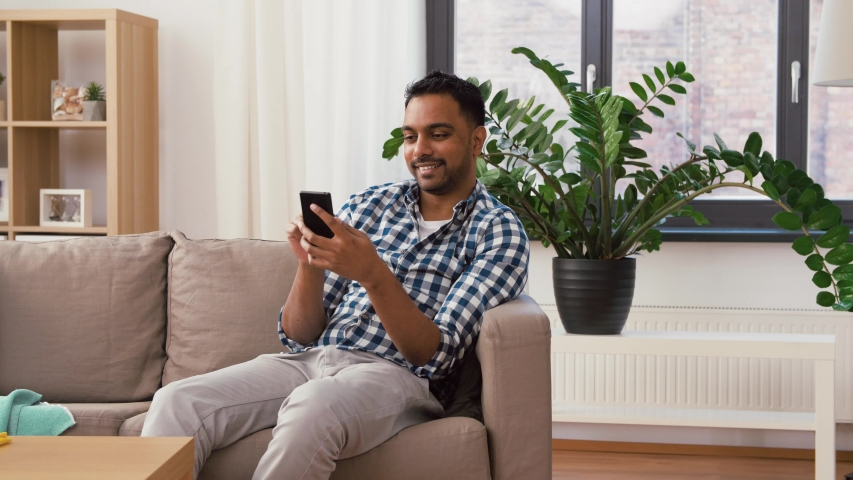 Household and technology concept - happy indian man using smartphone after cleaning home | Shutterstock HD Video #1029628925
