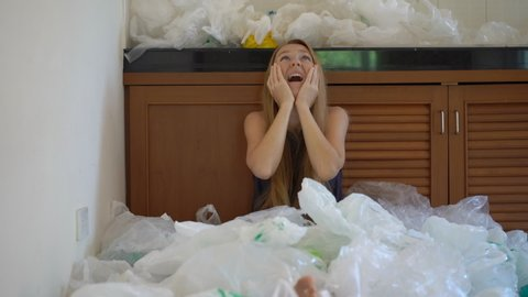 A young woman is covered with plastic bags and is horrified by the amount of plastic that he uses. The concept of environmental pollution by the plastic. Concept of plastic overuse