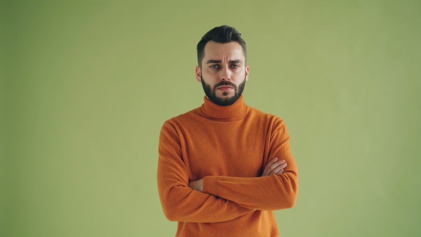 Portrait of unhappy male student looking at camera standing with arms crossed against green background. Upset young people and negative emotions concept. | Shutterstock HD Video #1029647975