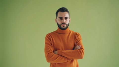 Portrait of unhappy male student looking at camera standing with arms crossed against green background. Upset young people and negative emotions concept.