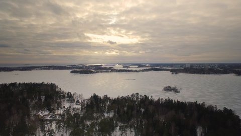 Aerial drone shot depicting the sheer mass and size of a frozen lake in Northern Finland during the winter season.