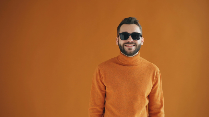 Portrait of trendy guy raising sunglasses and smiling looking at camera standing against orange background. Modern young people, flirtation and emotions concept.
