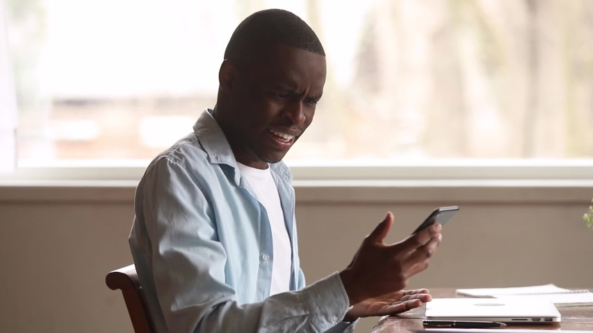 Mad stressed african man holding cellphone annoyed with mobile app error spam message on slow stuck broken smartphone, angry black guy frustrated by phone problem having complaints on bad service