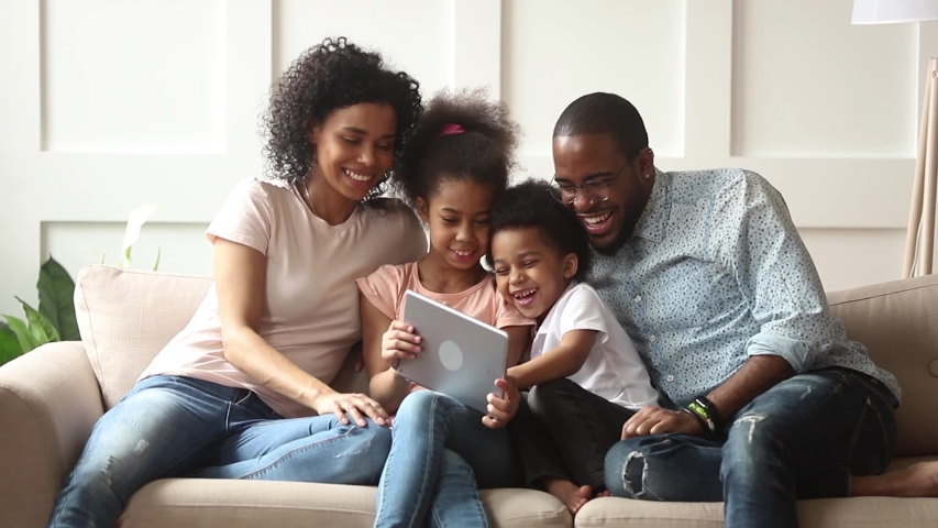 Cute little african children play online game using digital tablet having fun with parental control sit on sofa, happy black family laugh look at computer screen together enjoy do internet shopping