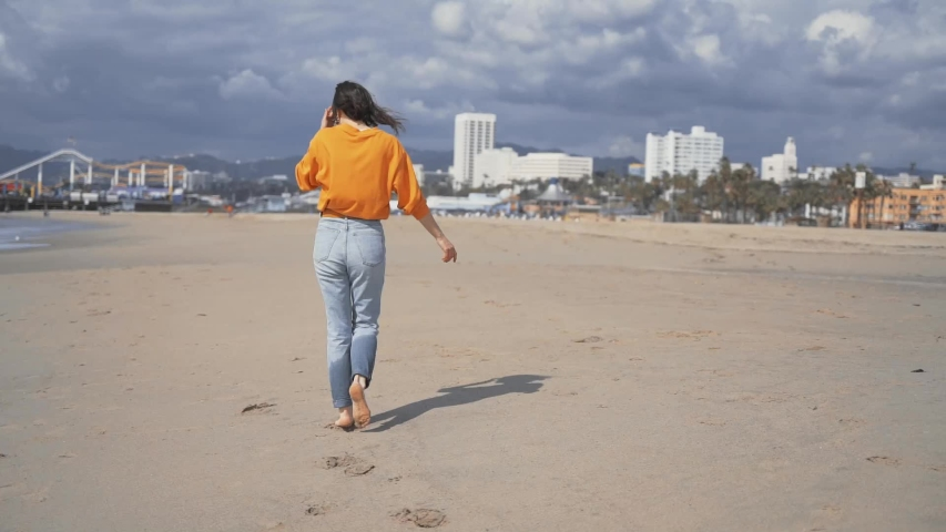 Happy barefoot girl on the beach in Los Angeles | Shutterstock HD Video #1029727565