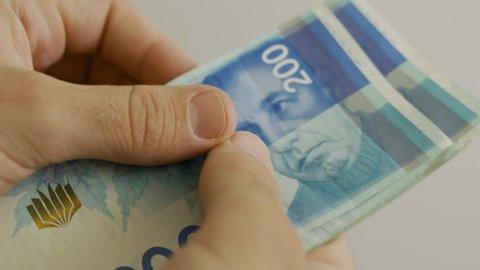 Counting 200 Israeli shekel bills - close up on large amount of money