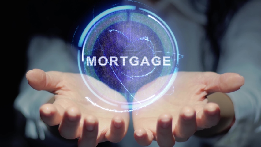 Female hands show a round conceptual hologram with text Mortgage. Unrecognizable woman in ashen white on a black background with future holographic technology