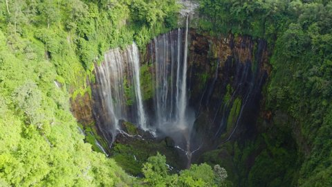Beautiful aerial landscape of Tumpak Sewu waterfall or Coban Sewu waterfall with Mount Semeru background. Shot in 4k resolution from a drone flying forwards