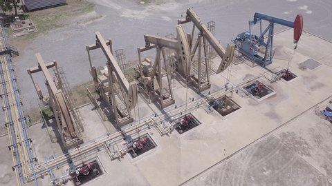 Drone Flight Past Working Pumpjack ndustrial oil pump jack working and pumping crude oil for fossil fuel energy with drilling rig in oil field
