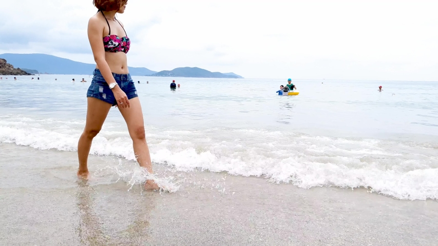 Low shot of woman strolling in the shallows of a tropical beach - finishing with a Medium Shot of Woman and beach. Shallow water foreground, tropical mountain background.
