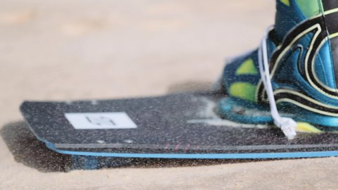 Kiteboarding board and boot on sandy terrain. Close up. Defocused.