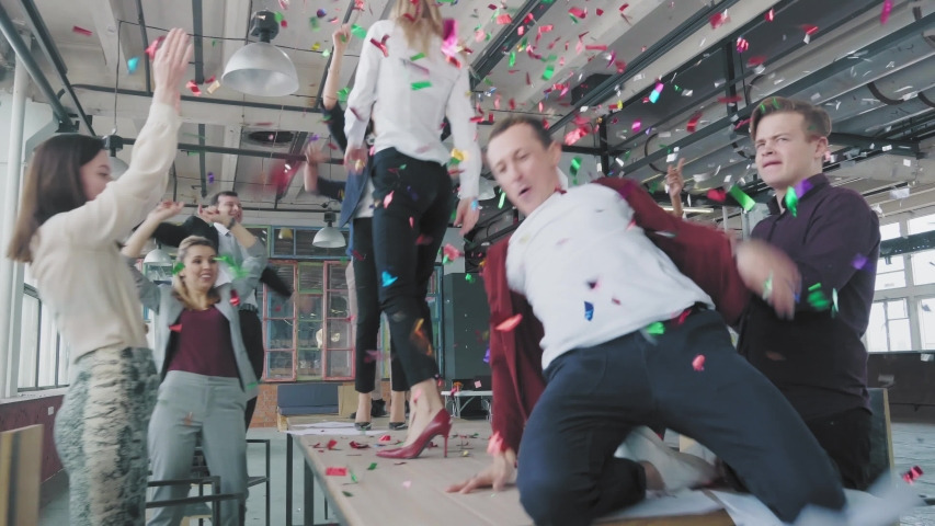 Employees celebrate the end of the project, have fun dancing on the table. His colleagues blow up flappers with confetti. Managers enjoy success and victory. Corporate party business team. Coworking   Shutterstock HD Video #1029925745