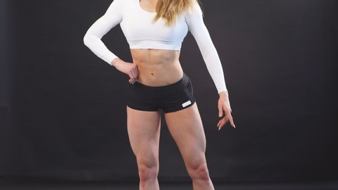 Strong muscular female bodybuilder in stylish sportswear posing to the camera. Isolated black background