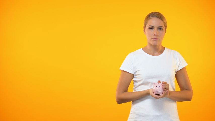 Sad young woman shaking piggybank, lack of money, financial problem, bankruptcy   Shutterstock HD Video #1029942785