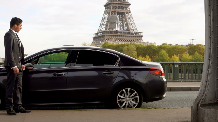 Business women with a suitcase goes and gets into the car next to the Eiffel Tower | Shutterstock HD Video #1029952085