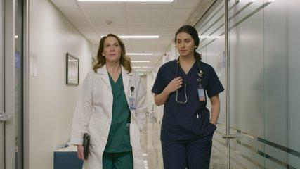 Slow motion of doctor and nurse walking and talking in hospital corridor / Salt Lake City, Utah, United States