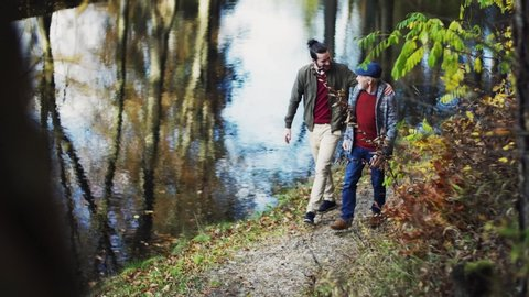 Senior father and his son walking in nature, talking.