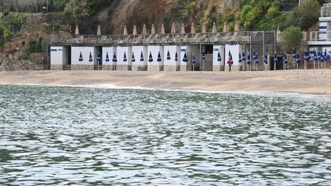 Lerici, La Spezia, Italy.  05/22/2019 Bathhouse on a sea bay. Rippled water surface and people walking on the beach. Bathhouse on a sea bay.