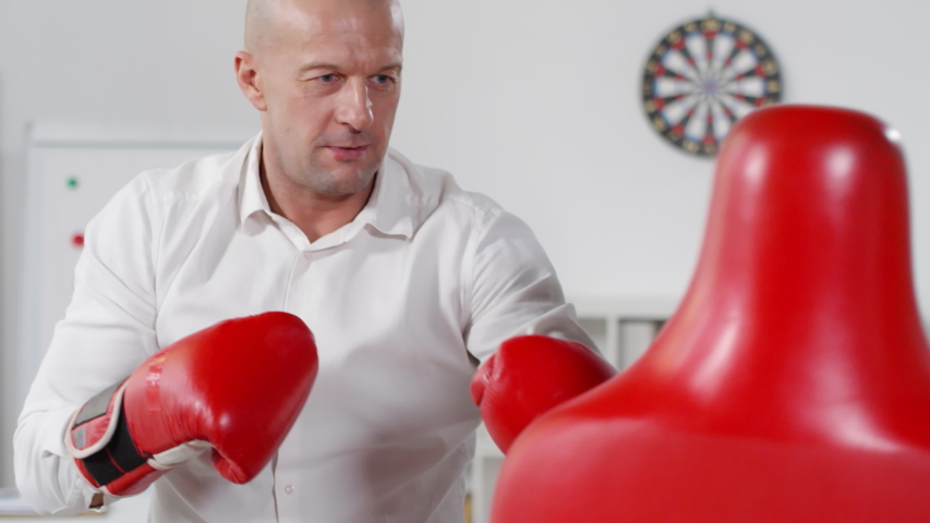 Chest-up shot of middle-aged employee with shaved head, wearing smart white shirt and boxing gloves, enjoying active lunch break and vigorously punching red dummy alone in open-space office | Shutterstock HD Video #1030090805
