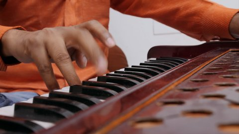 Side shot of Indian musician playing the harmonium.