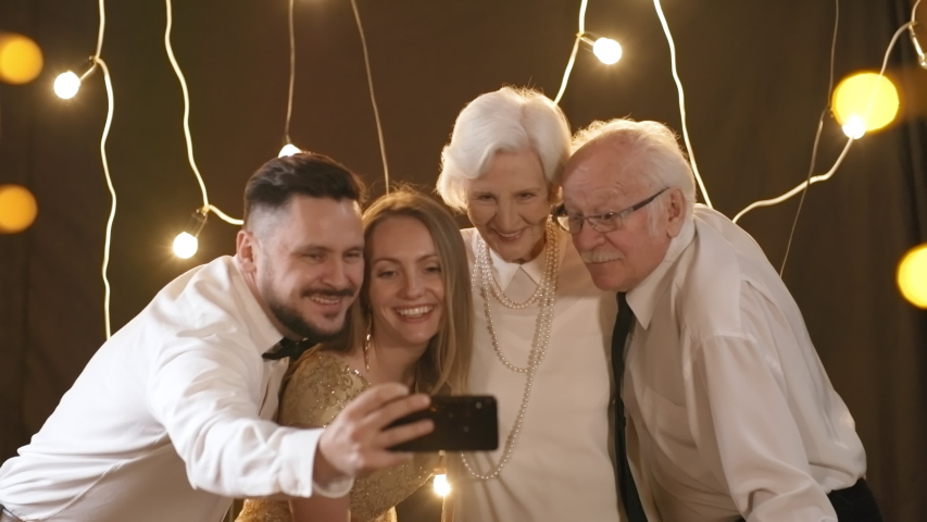 PAN shot of happy young man and his beautiful girlfriend taking selfie with elderly couple in room decorated with fairy lights   Shutterstock HD Video #1030110665
