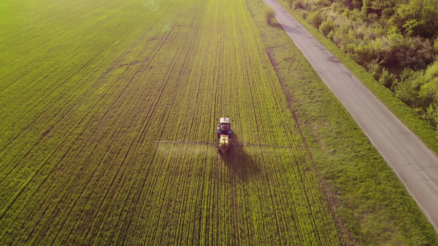 Aerial view of farming tractor spraying on field with sprayer, herbicides and pesticides at sunset. Farm machinery spraying insecticide to the green field, agricultural natural seasonal spring works. | Shutterstock HD Video #1030112525