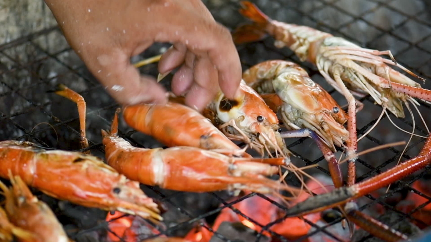 Chef is cooking delicious prawn and burnt shrimp grill with flames on oven stove eat with seafood sauce,Thai sea food.   | Shutterstock HD Video #1030117565