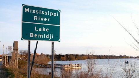 Road Sign at bridge over Mississippi River at Lake Bemidji in early morning Fishing Opener with people trying to catch fish on pier and in boats and town of Bemidji Minnesota in background.