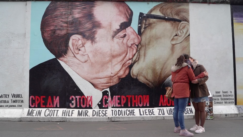 "Berlin, Germany - 13 May 2019. Girls kissing in front of the graffiti ""Socialist fraternal kiss"". East Side Gallery at sunset"