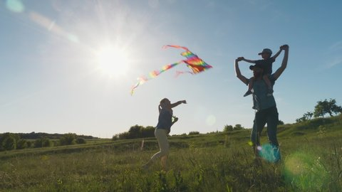 Happy family, father with his little son on his shoulders and daughter are walking in nature, launching an air kite. Slow motion shot. Blue sky and bright sun in the background