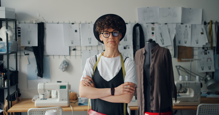Portrait of independent young woman clothes designer standing in studio with arms crossed looking at camera. Successful youth and small business concept. | Shutterstock HD Video #1030159445