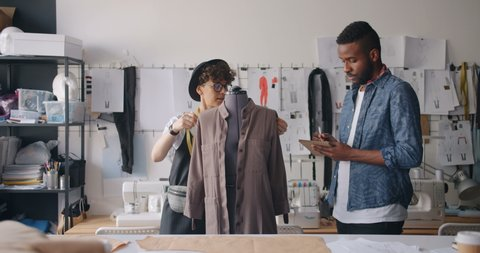 African American man and Caucasian girl tailors are measuring clothes on dummy writing measurements in notebook working in modern studio. People and work concept.