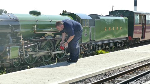 Dungeness Kent England May 2019. Mechanic oiling the wheels on one of the Romney, Hythe and Dymchurch 15 in gauge trains while stationary at Dungeness Station.