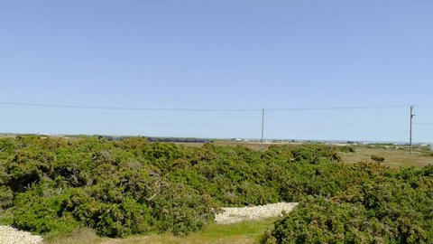 Dungeness Kent England May 2019.  Romney, Hythe and Dymchurch 15 in gauge train leaving  Dungeness Station. Long view across dunes and nature reserve.
