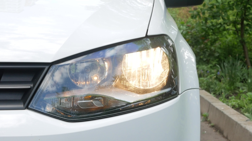 Close up shot of blinking headlights in car