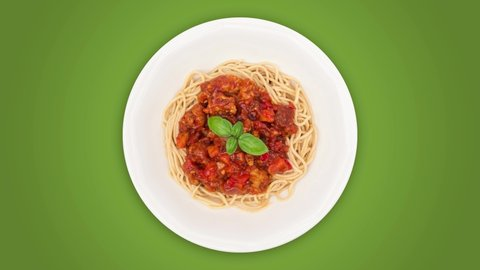 Rotating spaghetti bolognese on white plate against green background, top view, seamless loop, 4k