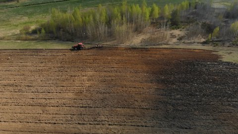 Aerial view on the side of a powerful red tractor with a plow, agricultural machine, performing processing, plowing, cultivation of dark soil on the background of a magnificent picturesque nature