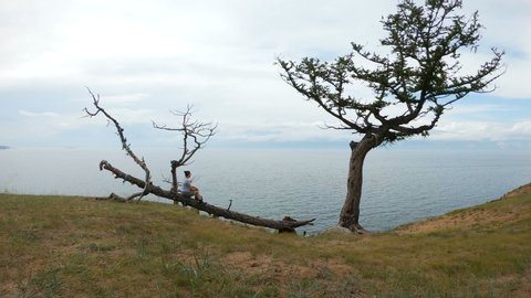 Girl sitting on a tree on the shore of lake Baikal. Aerial shot