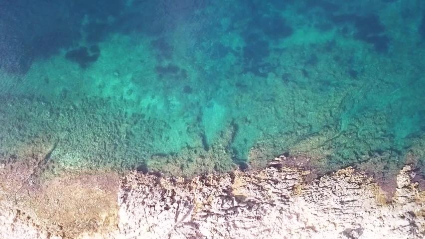 Birdseye view looking down at waves crashing into rocky shoreline Albania Riviera   Shutterstock HD Video #1030306565