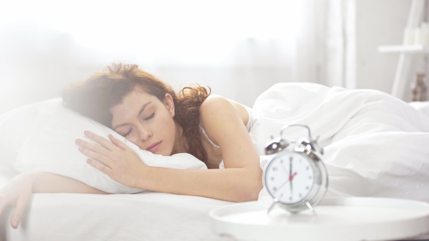 Beautiful girl lying in bed, turning off alarm clock and covering with blanket in morning | Shutterstock HD Video #1030403285