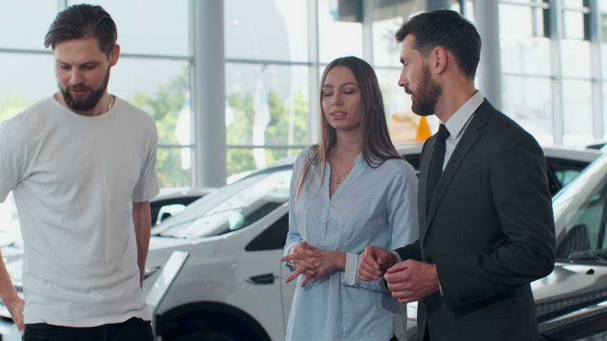 Professional car salesman is telling interested buyers beautiful couple about luxurious car in motor show while man and woman are looking at auto and listening to dealer.