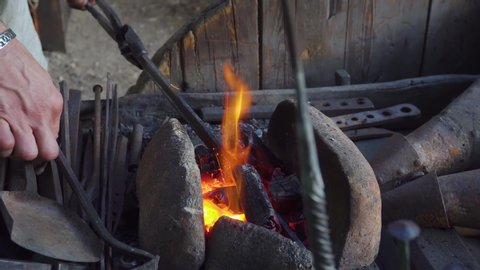 Blacksmith working with blacksmith furs in forge. Hot metal part in fire, then on stithy.