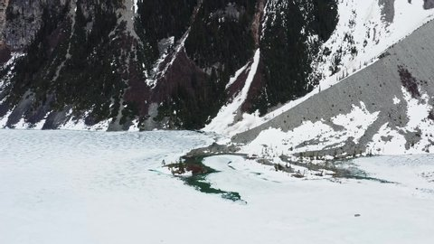 Aerial drone pull-up shot revealing the snow covered mountains and trees at the Joffre Frozen Lake in Pemberton, British Columbia, Canada.